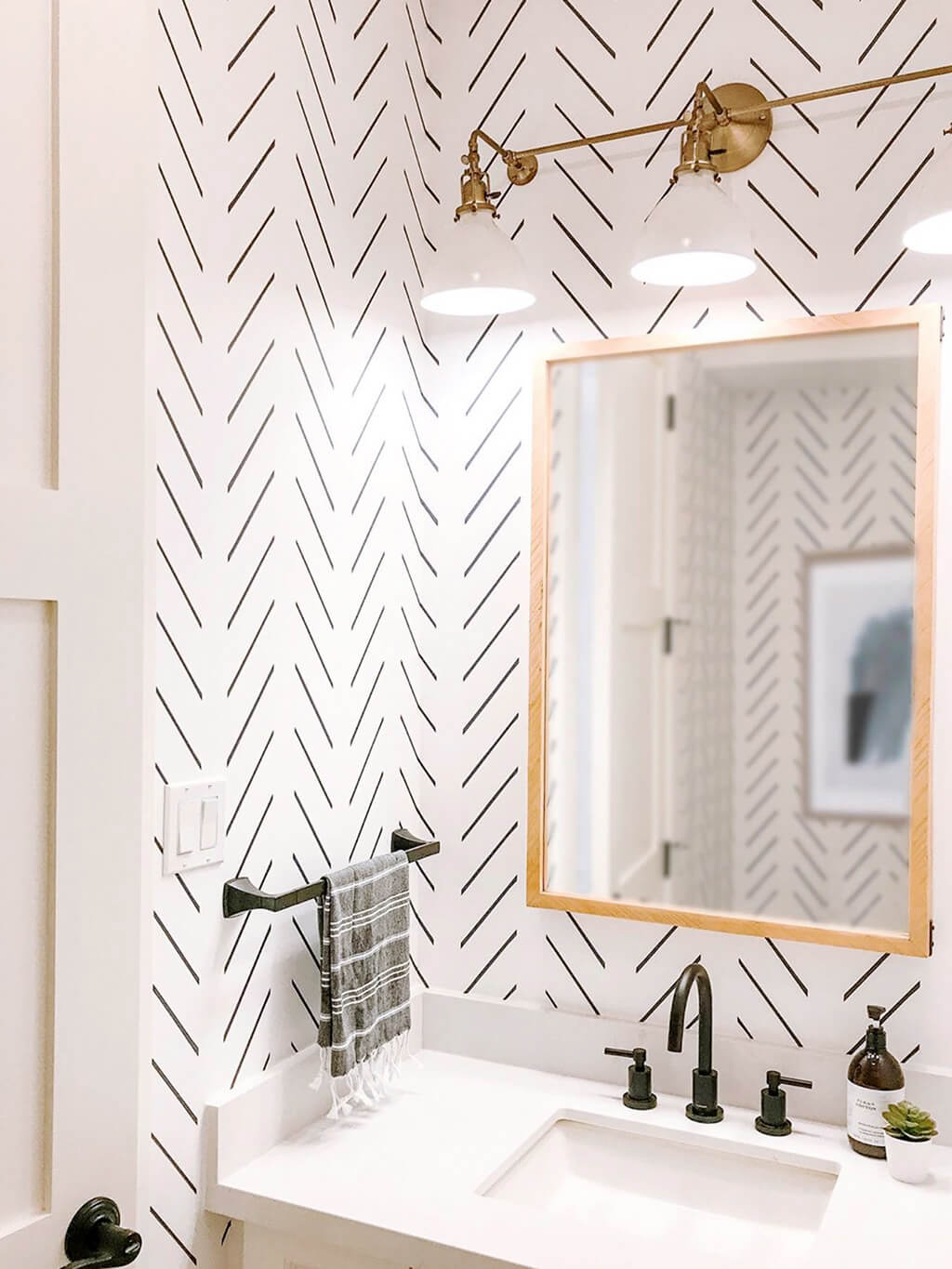 Small white powder room interior with modern herringbone design removable wallpaper, brass decor and black hardware