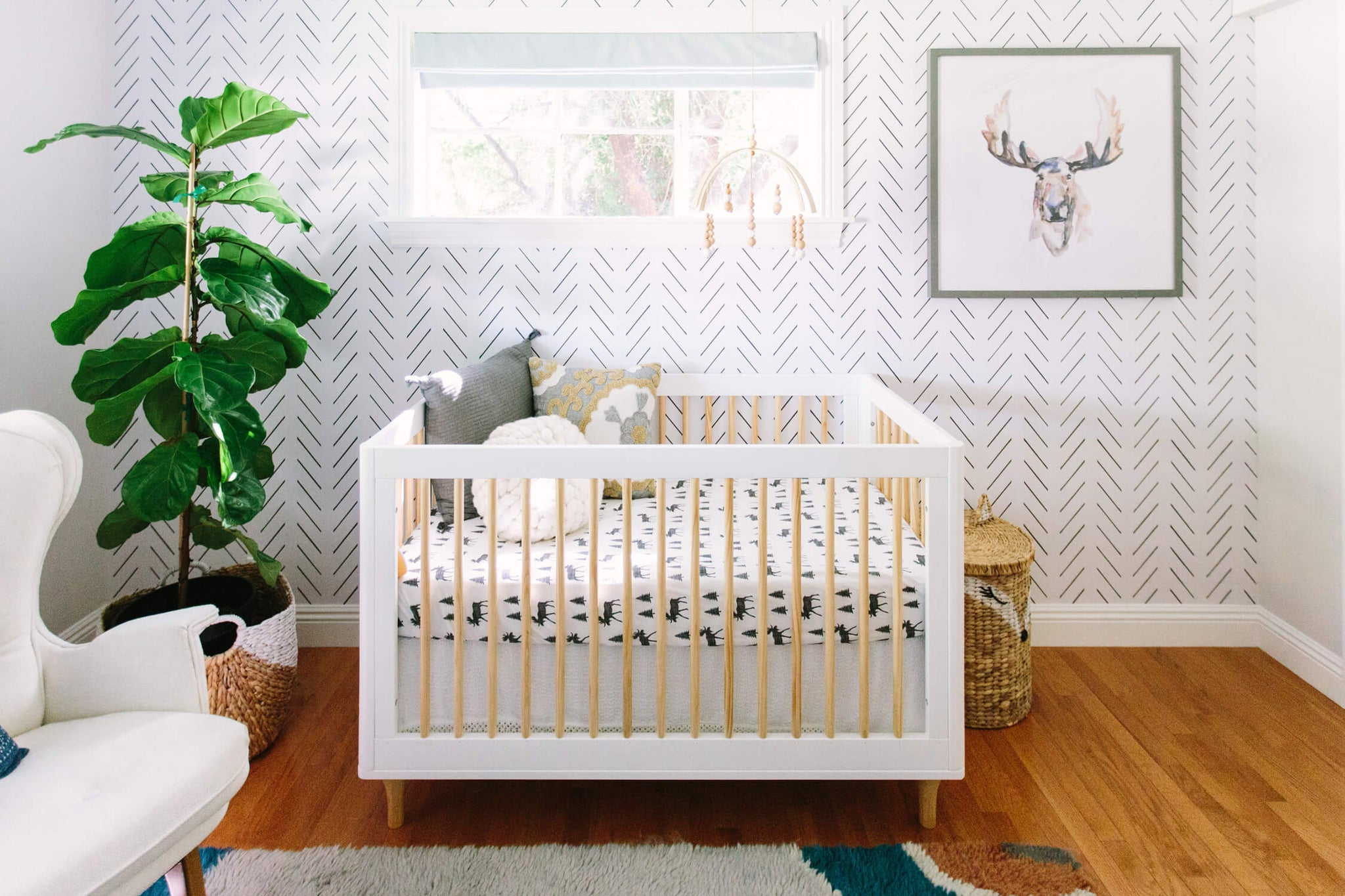 Modern woodland theme nursery for baby boy with herringbone removable wallpaper, moose art print, and colorful area rug.