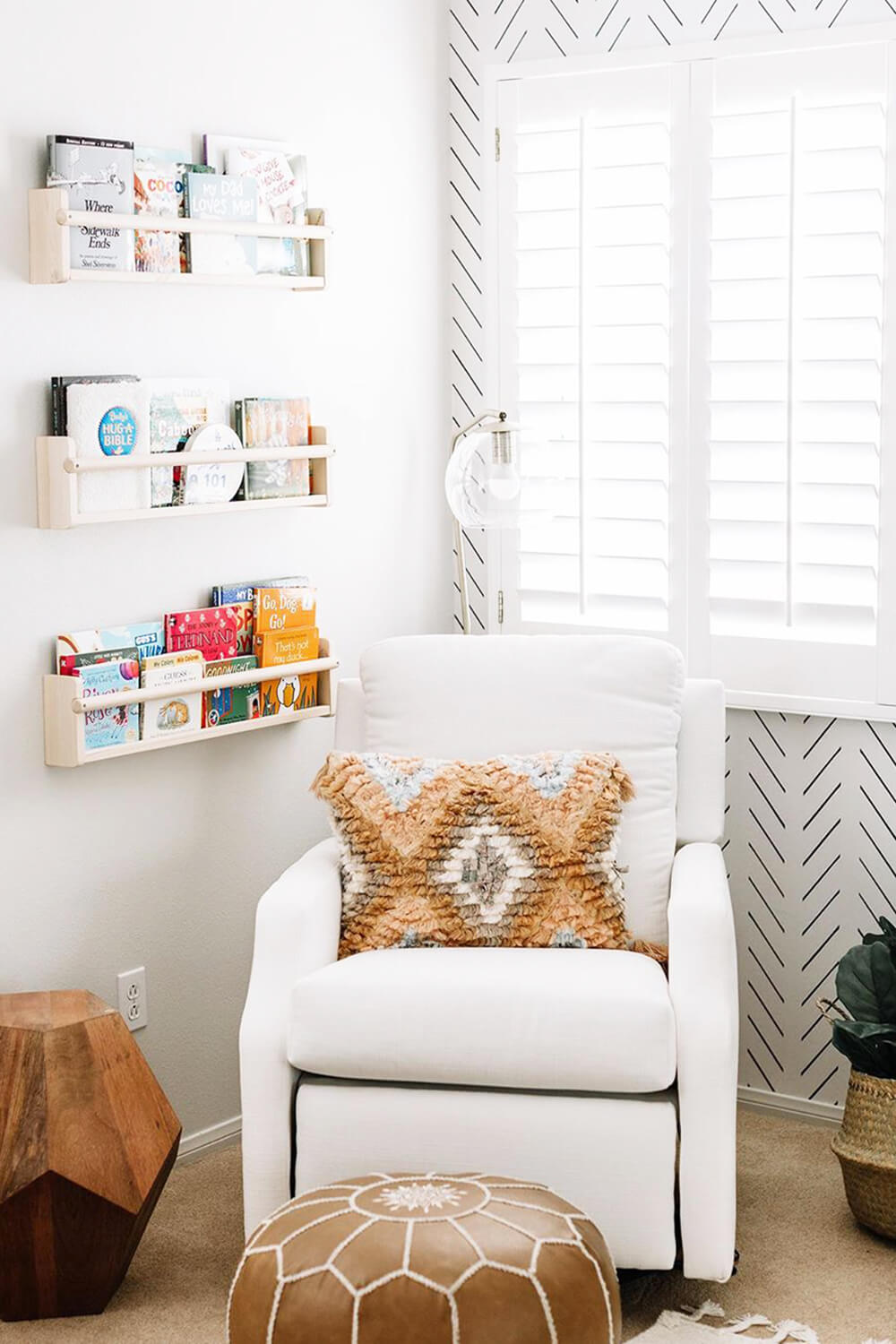 White boho nursery interior with white armchair, bohemian nursery decor and floating shelves