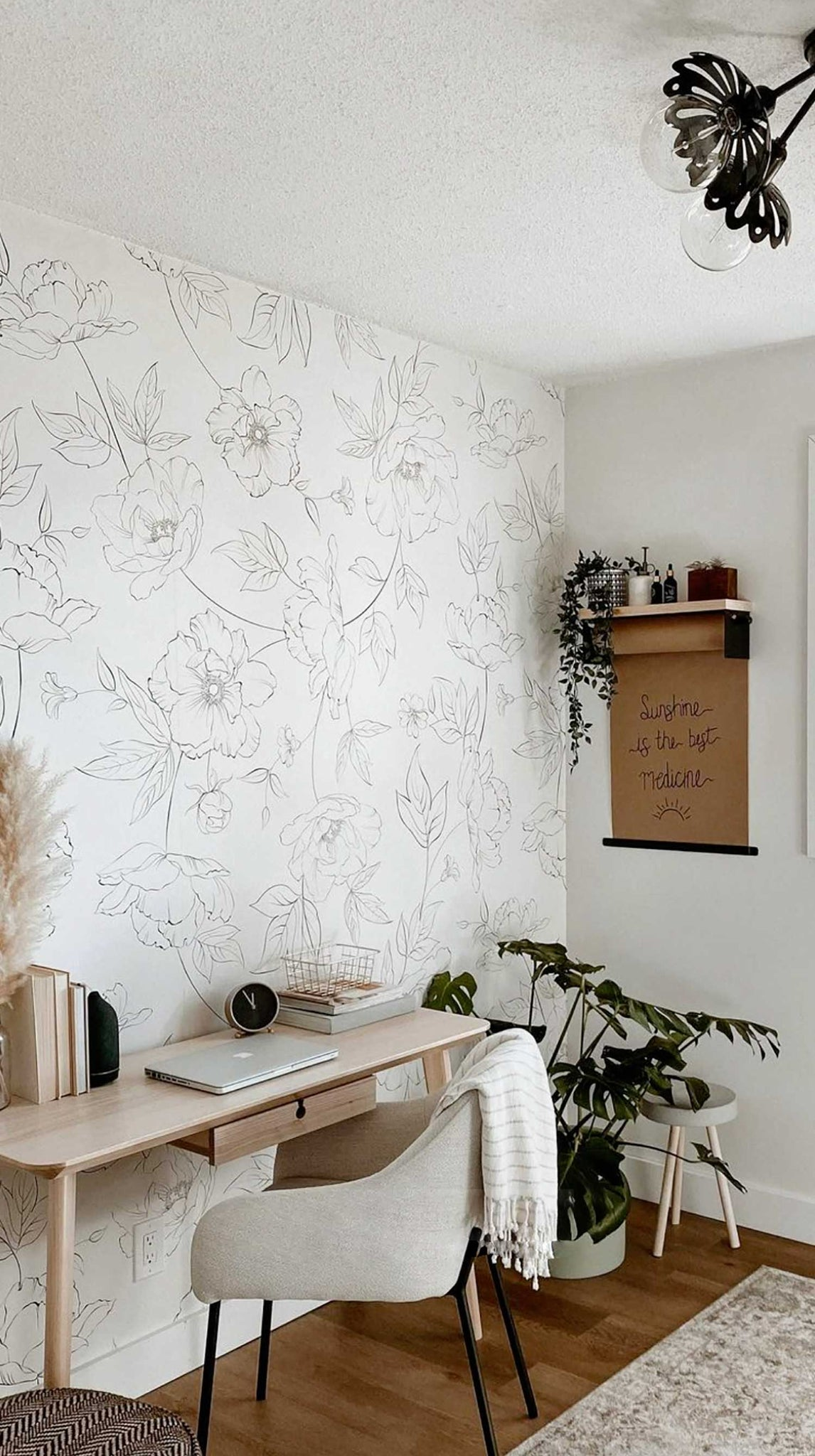 Modern boho style home office interior with floral wallpaper accent wall behind desk