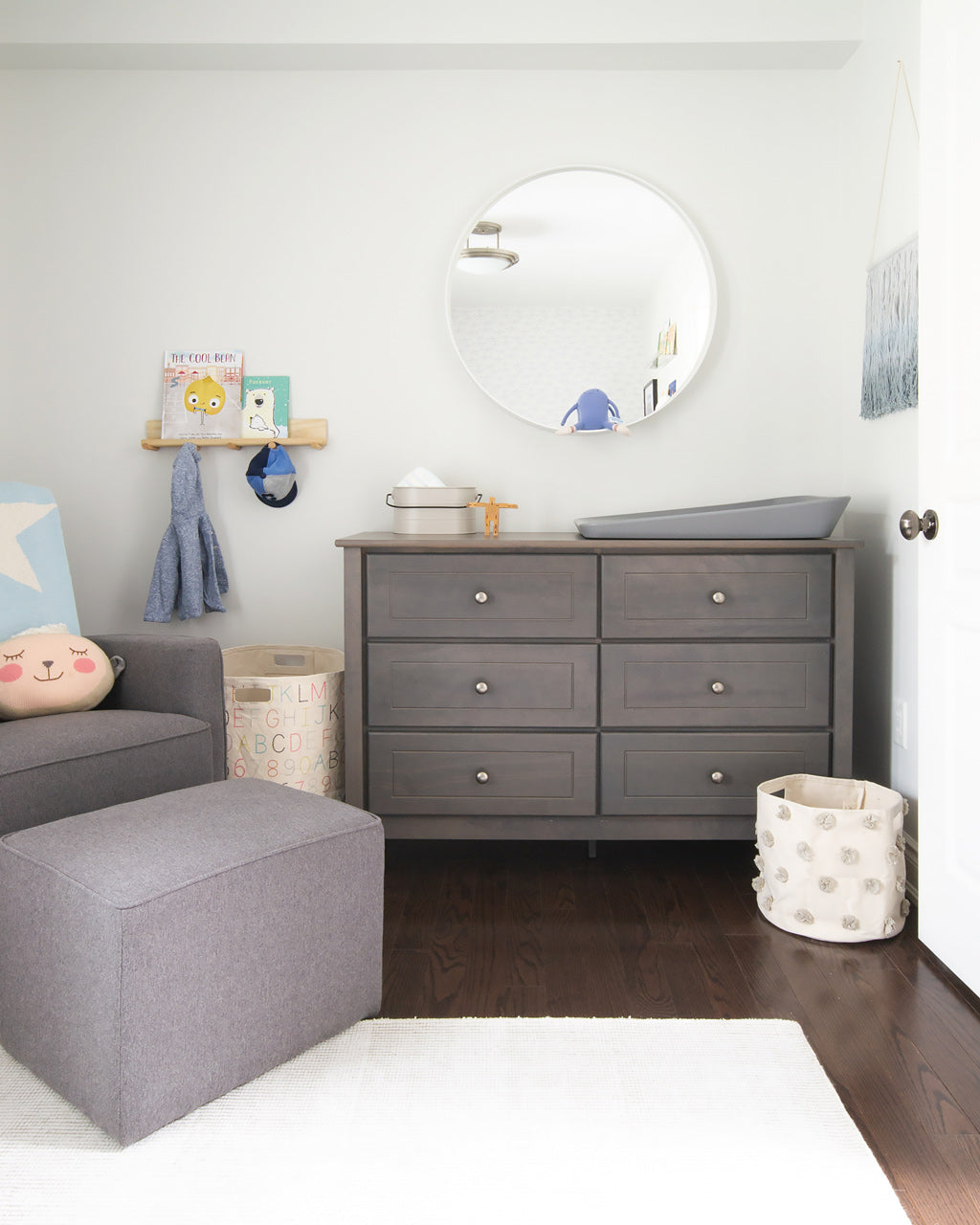 Nursery rocking chair and dresser in neutral grey color palette in white coastal theme nursery for baby boy