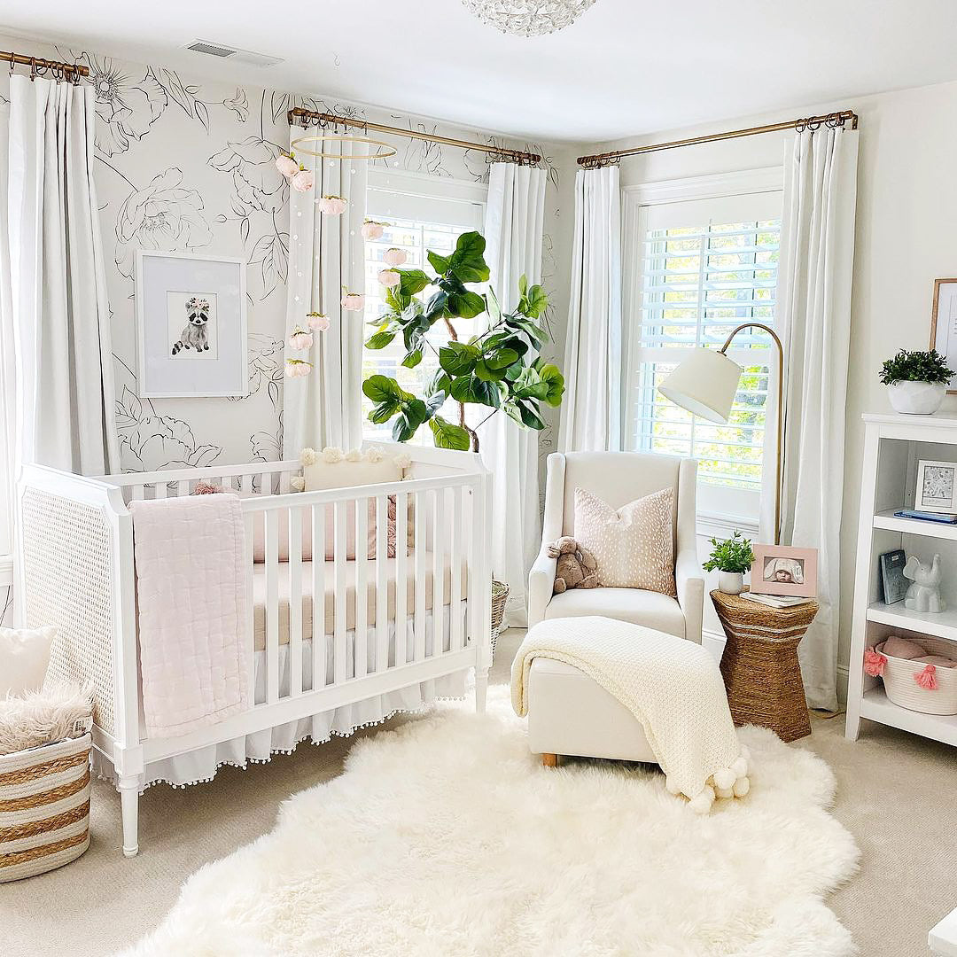 White and gold nursery interior with floral wallpaper as accent wall