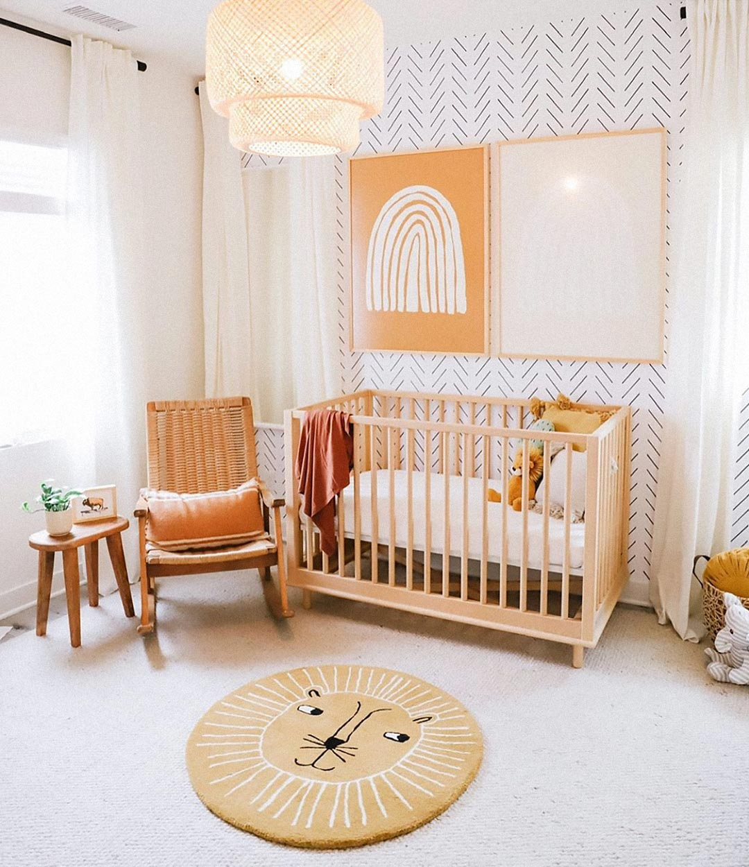 Rainbow baby nursery interior with white and mustard color scheme, self adhesive wallpaper with modern herringbone design print, jungle baby room theme and rainbow posters