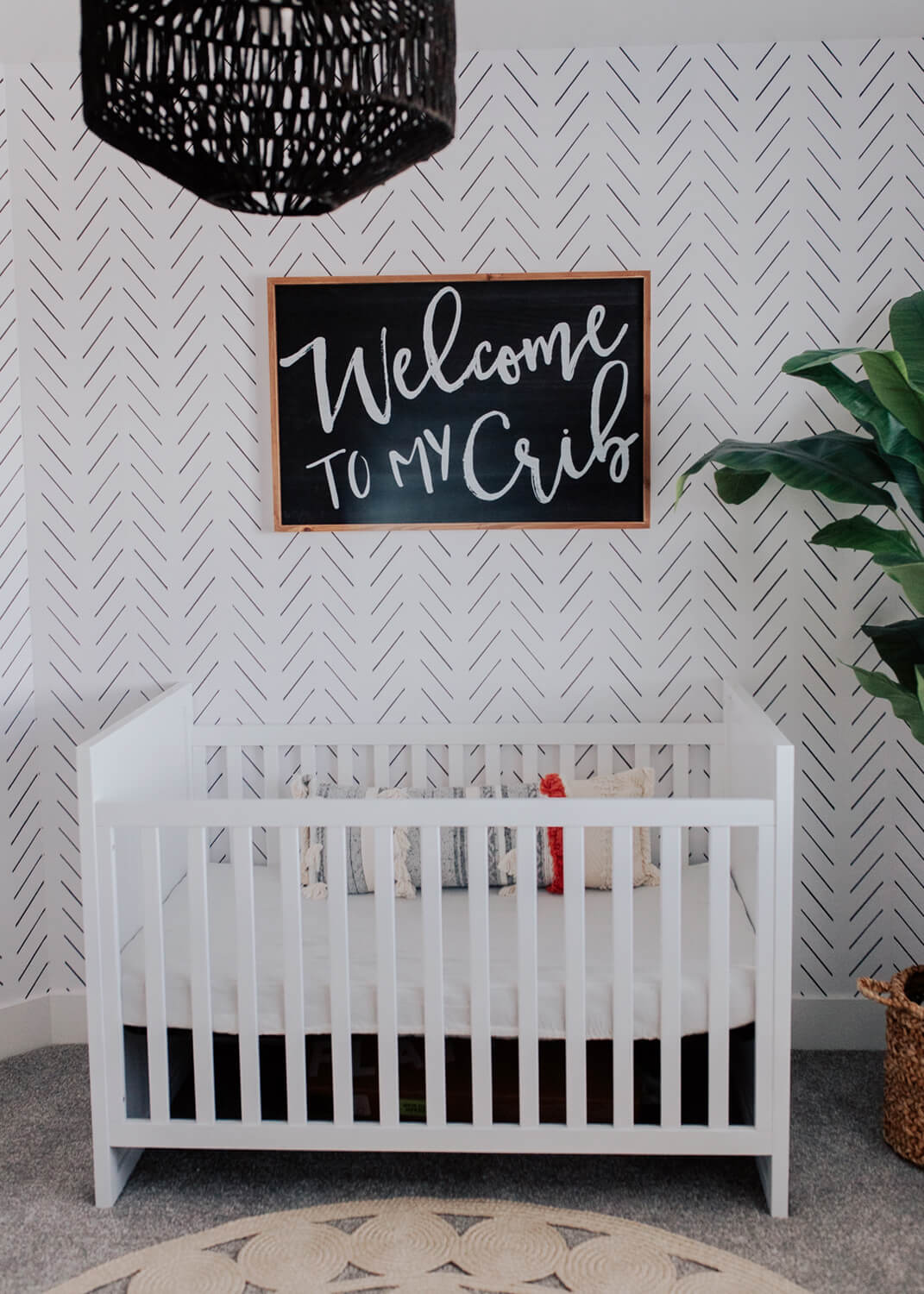 Modern black and white bohemian nursery with herringbone removable wallpaper and crib sign