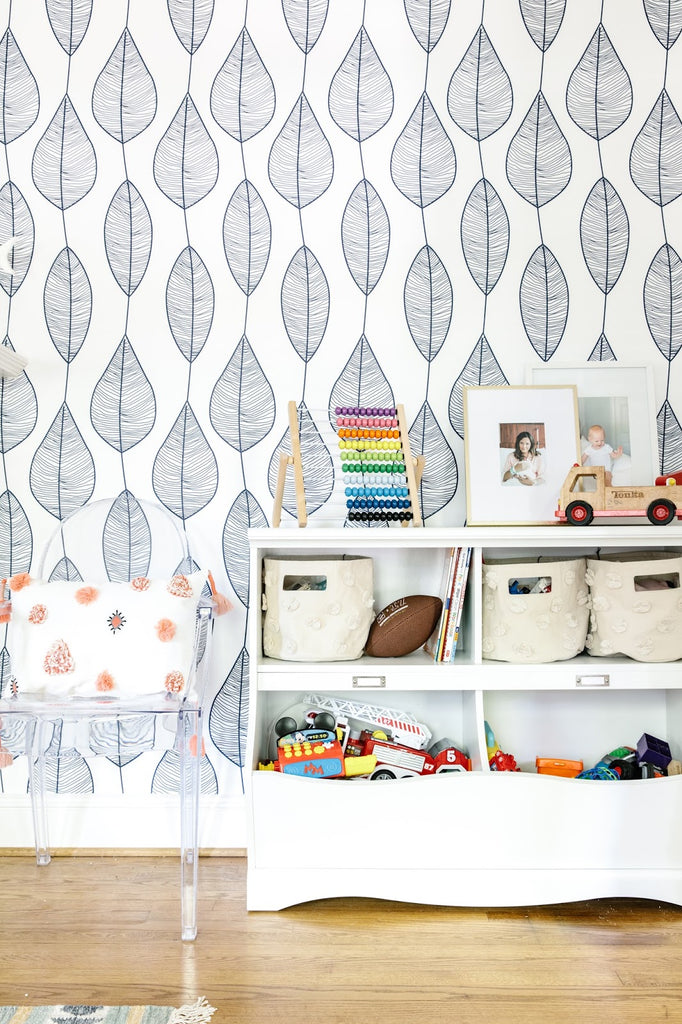 Stripy leaf wallpaper in kid's playroom interior with ghost chairs and white toy storage shelves