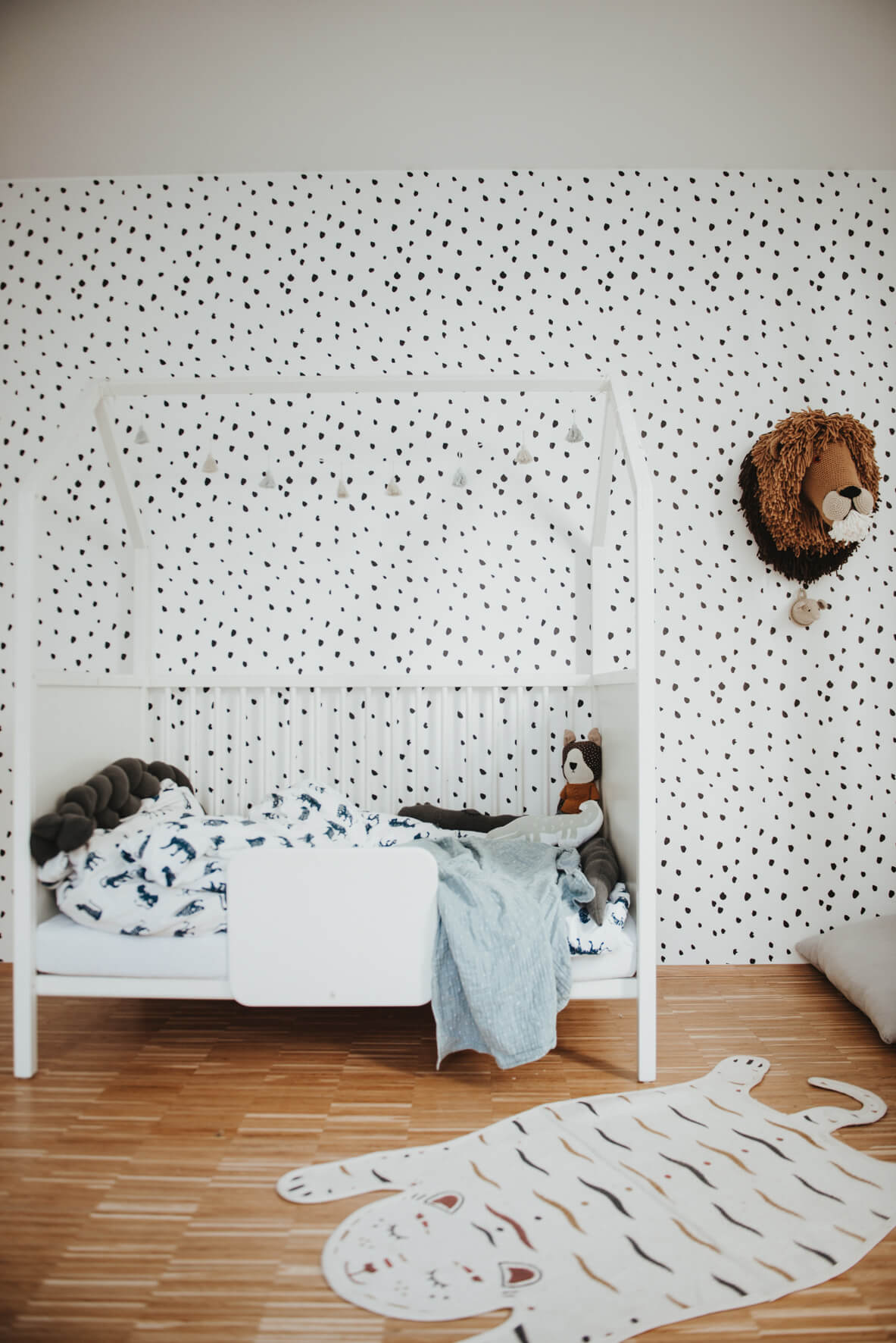 Black and white boys bedroom with white house shaped bed, animal spots removable wallpaper and tiger rug