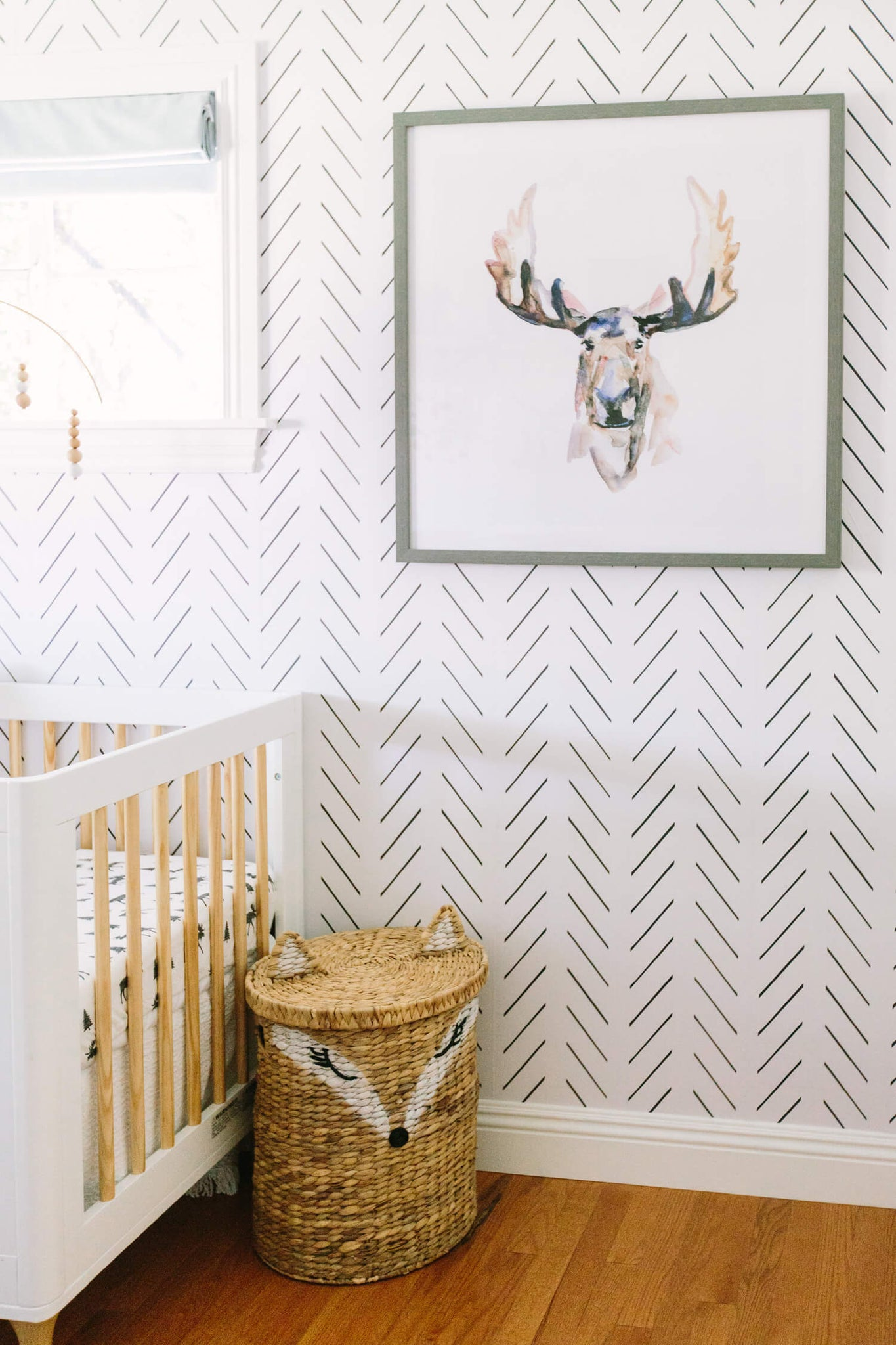 Black and white herringbone removable wallpaper in baby nursery with white crib, watercolor moose art print and fox rattan basket.