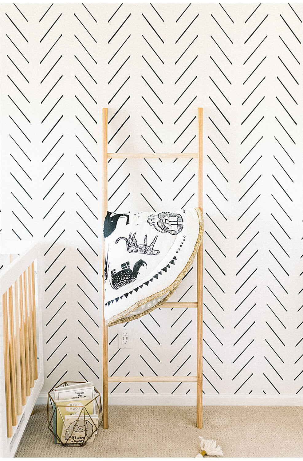 Herringbone removable wallpaper accent wall in modern baby boys nursery interior