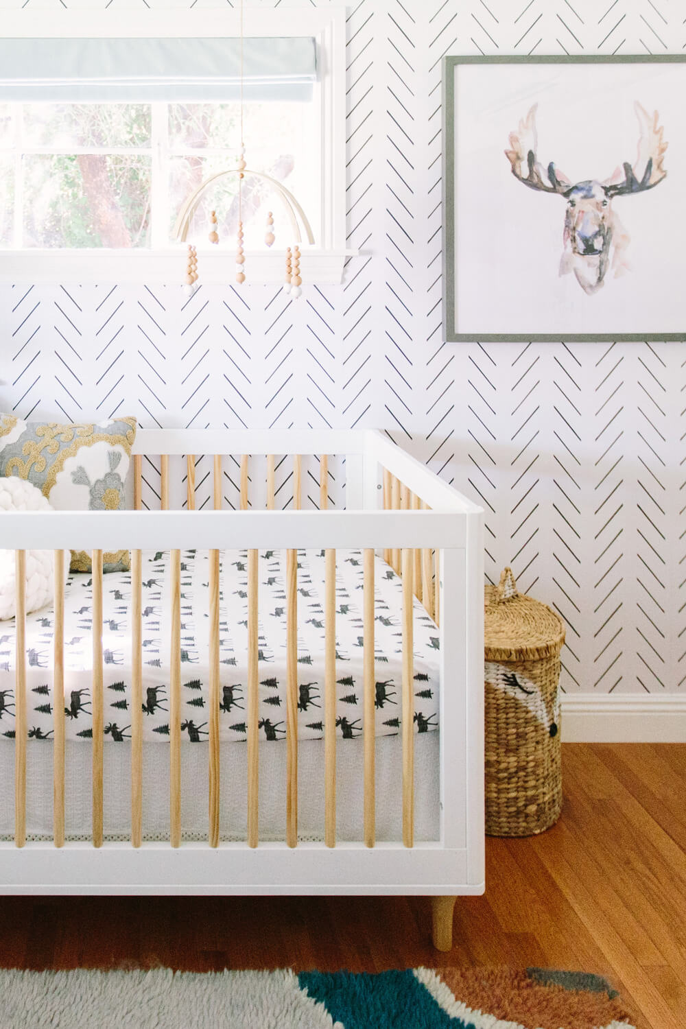 Modern woodland theme nursery with forest animals crib sheets, moose art print and herringbone removable wallpaper