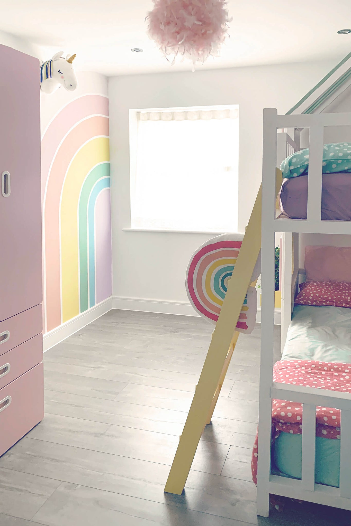 Soft pastel color rainbow unicorn themed girl's room interior with removable wallpaper