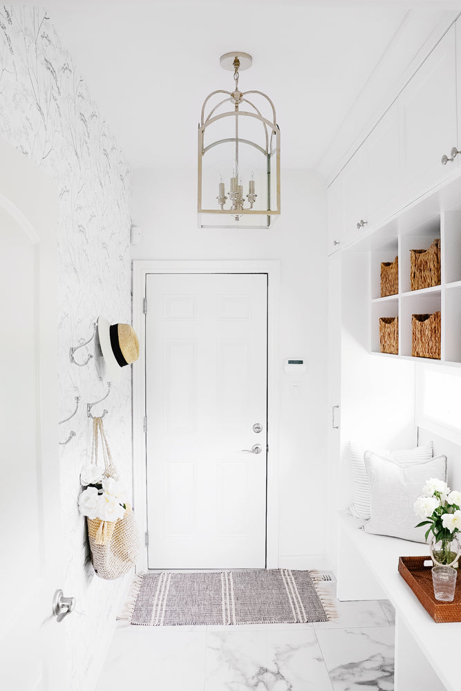 Modern white mudroom interior styled with wildflower removable wallpaper and natural woven interior pieces