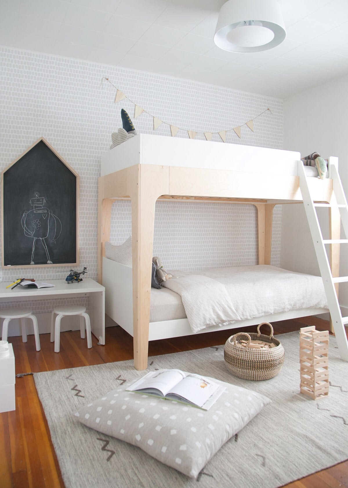 Modern boys room with light wood bunk bed, natural linen bedding, gender neutral removable wallpaper and white furniture
