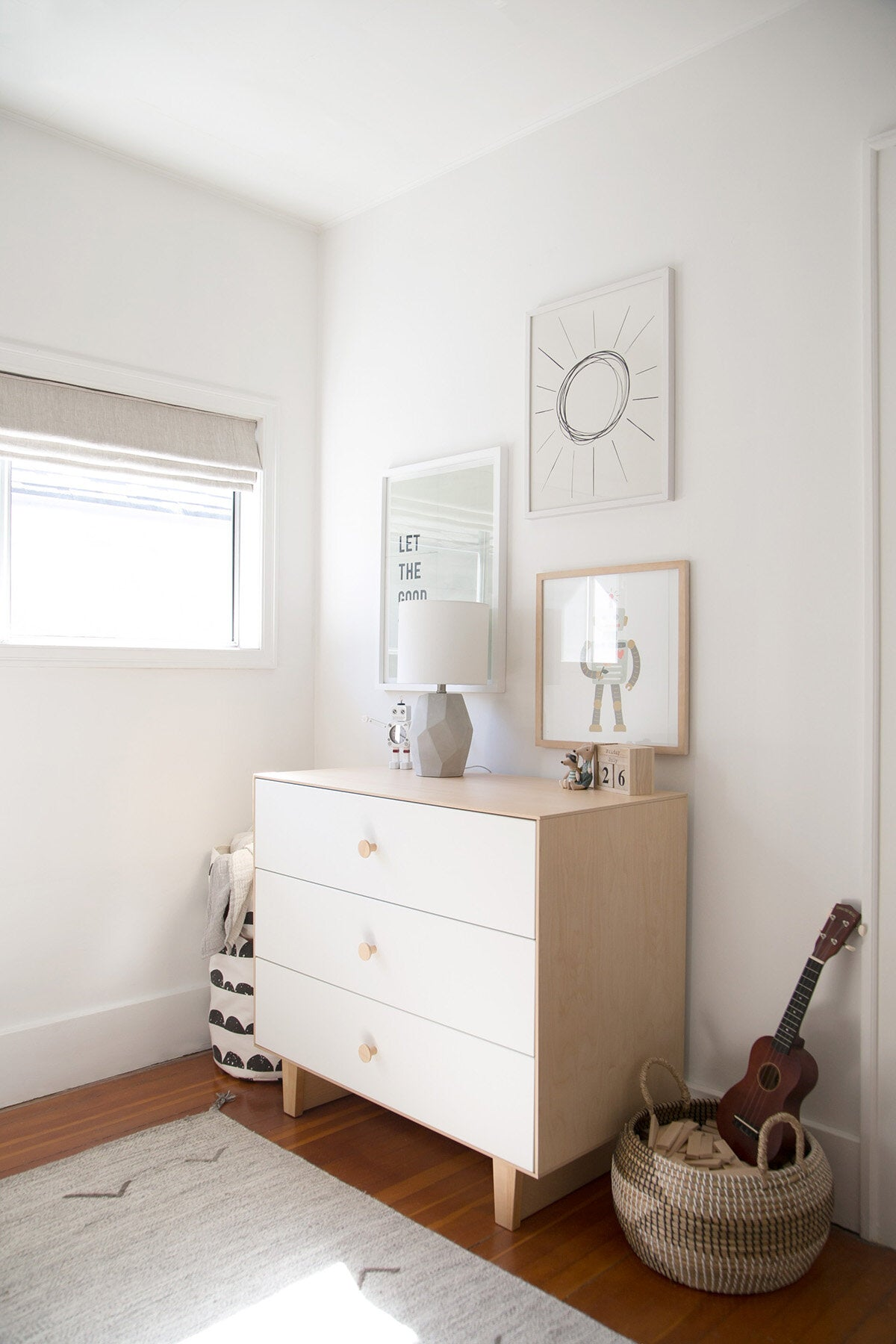 Light wood dresser in white boys bedroom interior with robot themed gallery wall