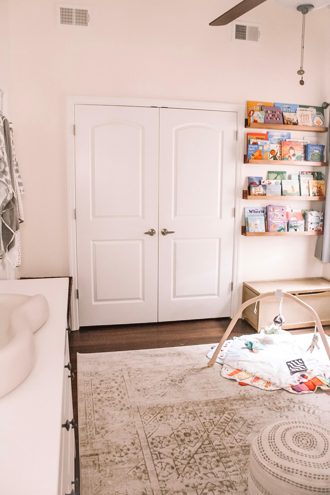 Nursery reading nook with floating shelves and book display