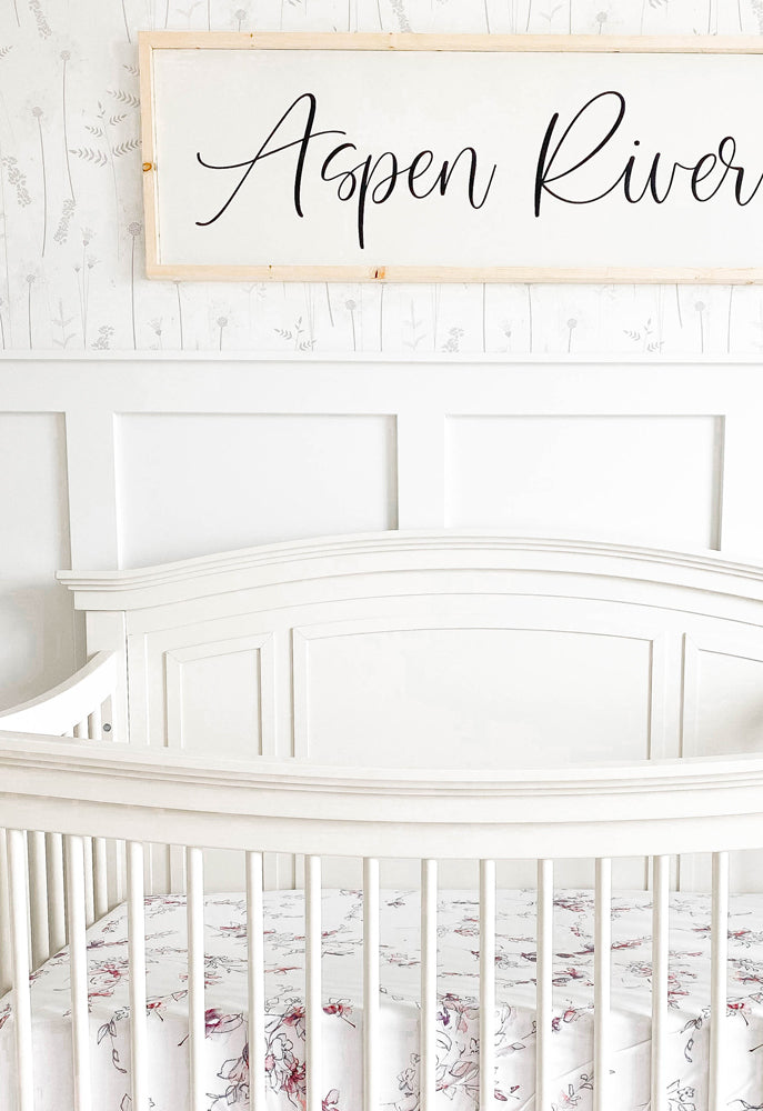 White crib nursery with pink decor and grey delicate flower wallpaper