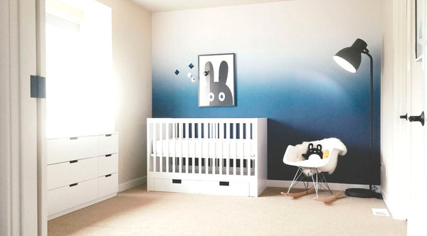 Nursery interior project with ombre wallpaper, white crib and Eams rocking chair