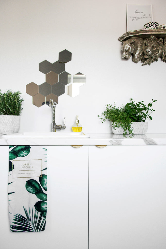 White office kitchen with hexagon mirrors and fresh herbs next to farmhouse sink