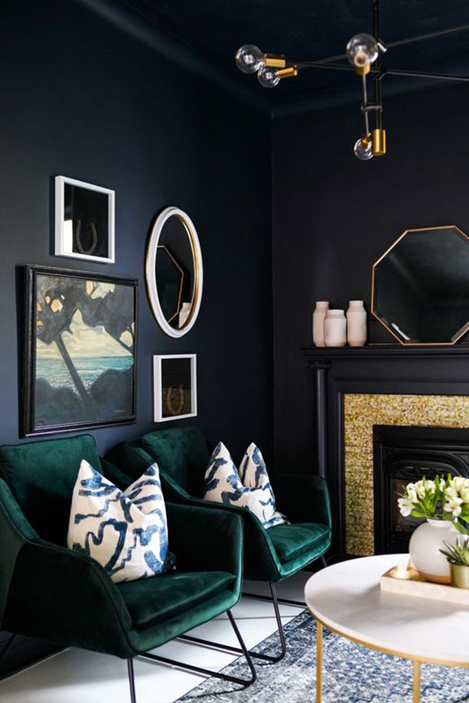 Moody living room with dark green velvet chairs.