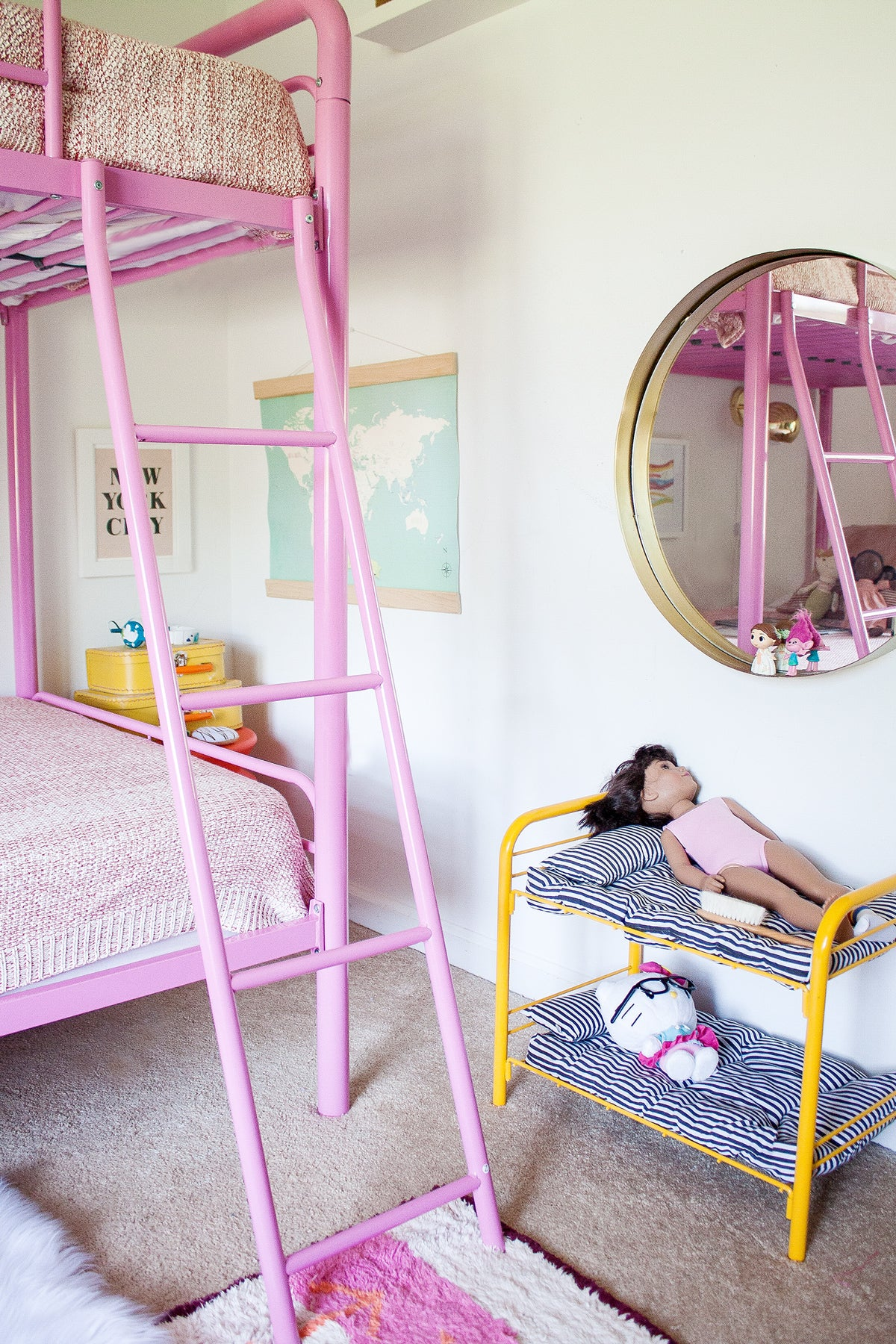 Girl's bedroom with pink bed and round brass mirror