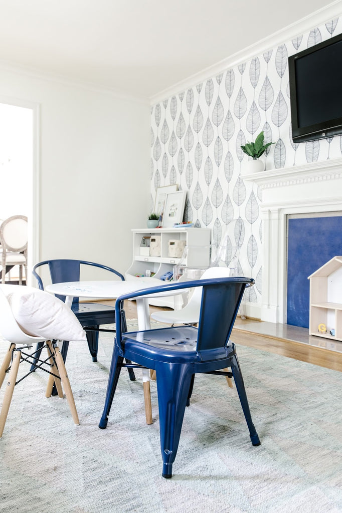 Kids playroom art station with blue metal chairs and white table on a moroccan rug