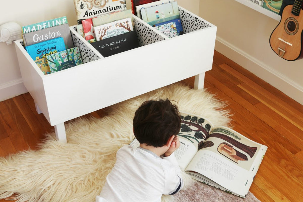 Boy reading a book in a kids room reading corner