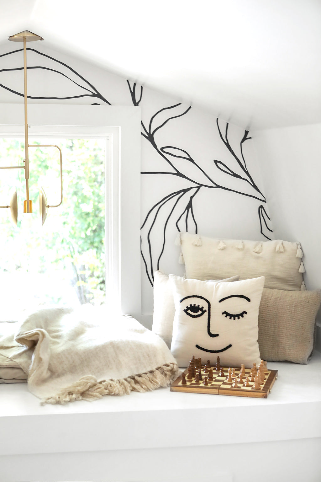 Wallpapered reading nook with cute pillows and wall mural