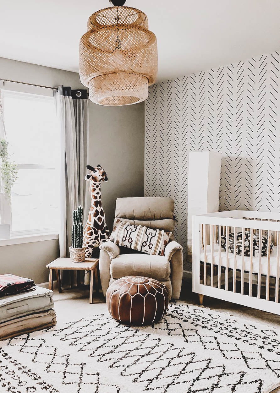 Safari themed nursery with tribal patterns, giraffe plush toy, herringbone removable wallpaper and boho decorative pillows