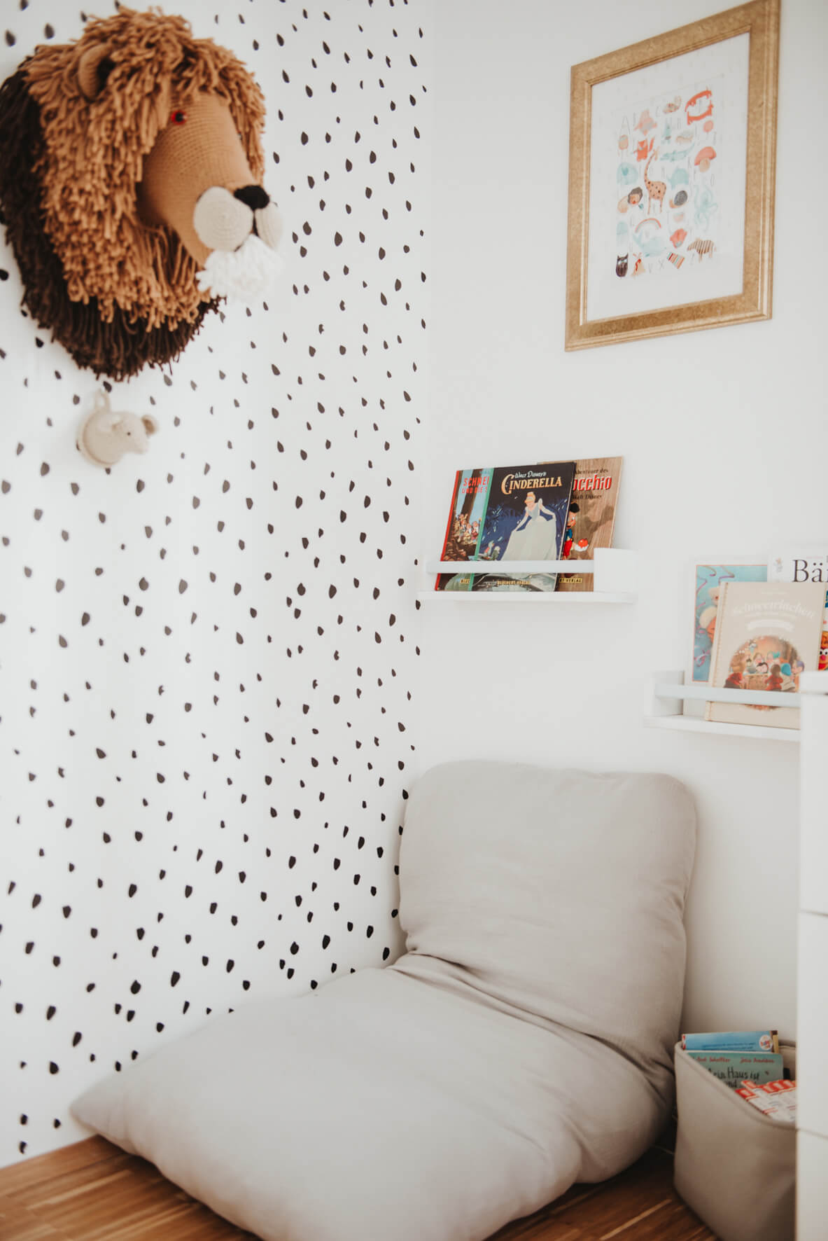 Reading nook in scandianvian kid's room with white floating shelves, book display and animal print removable wallpaper