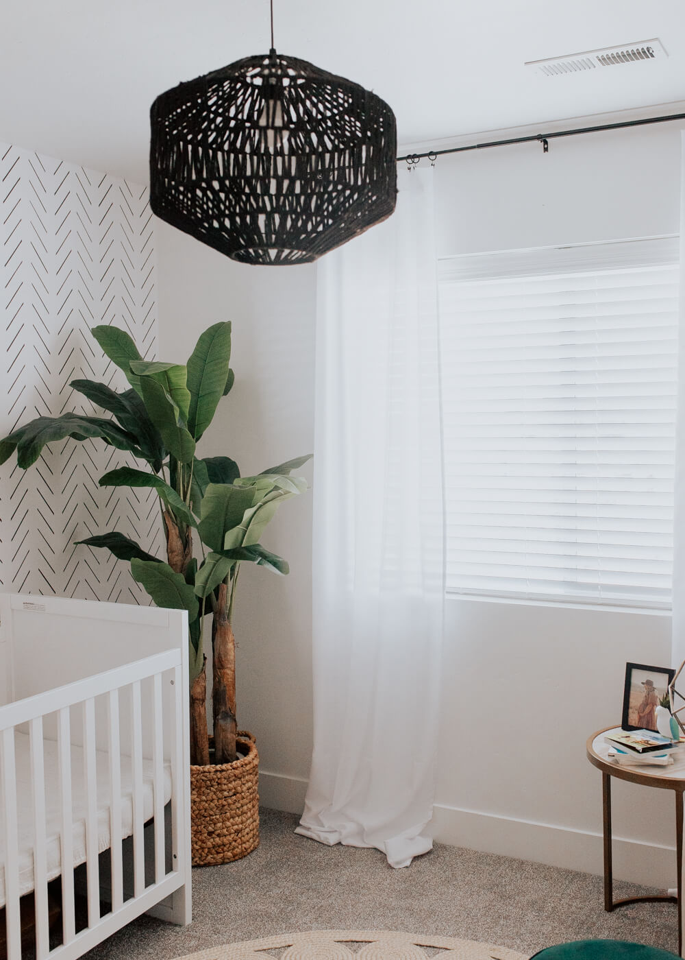 Modern minimal nursery design with black boho decor, removable wallpaper and banana leaf palm tree