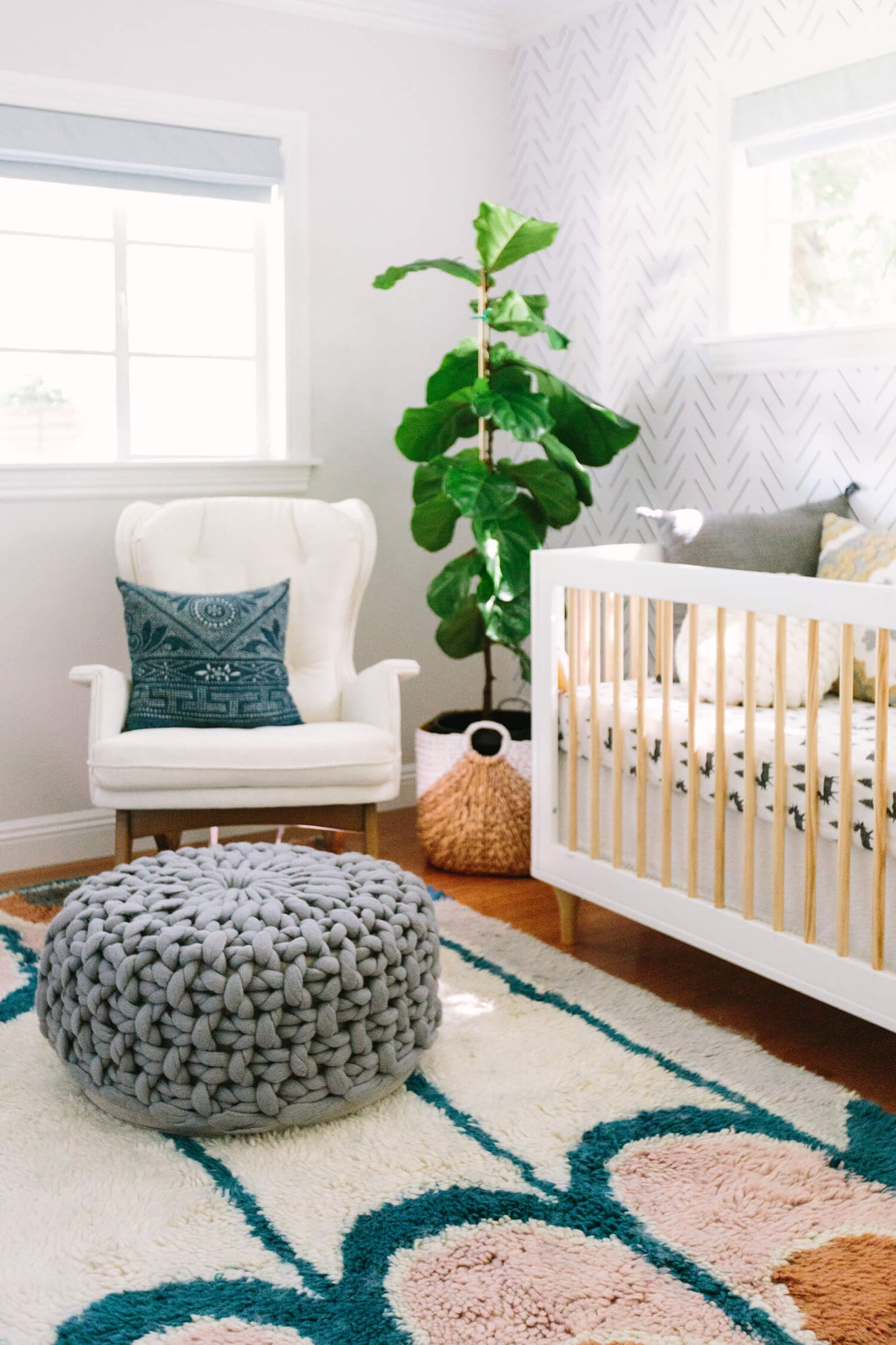 Gender neutral baby room with white rocking chair, colorful accents, removable wallpaper and forest animal theme.