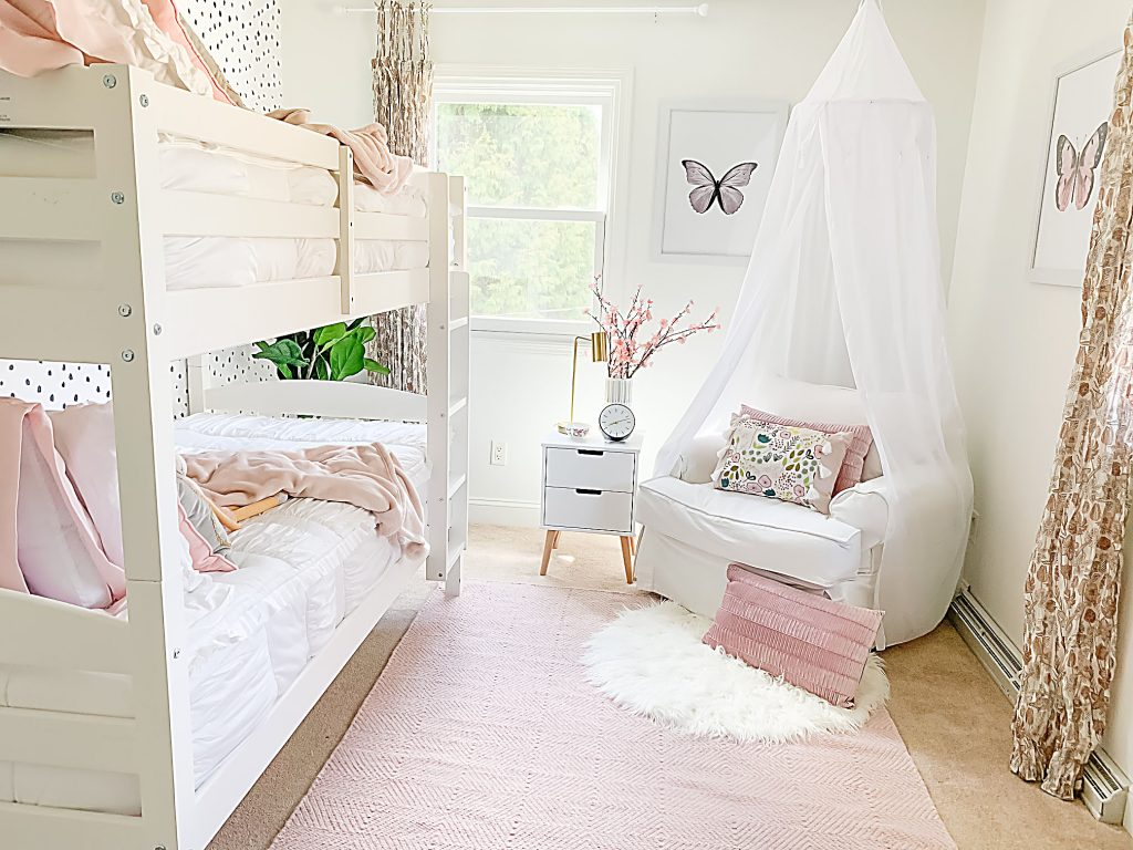 Shared girls bedroom with white bunk bed, modern removable wallpaper, pink ruffle bedding and modern white furniture