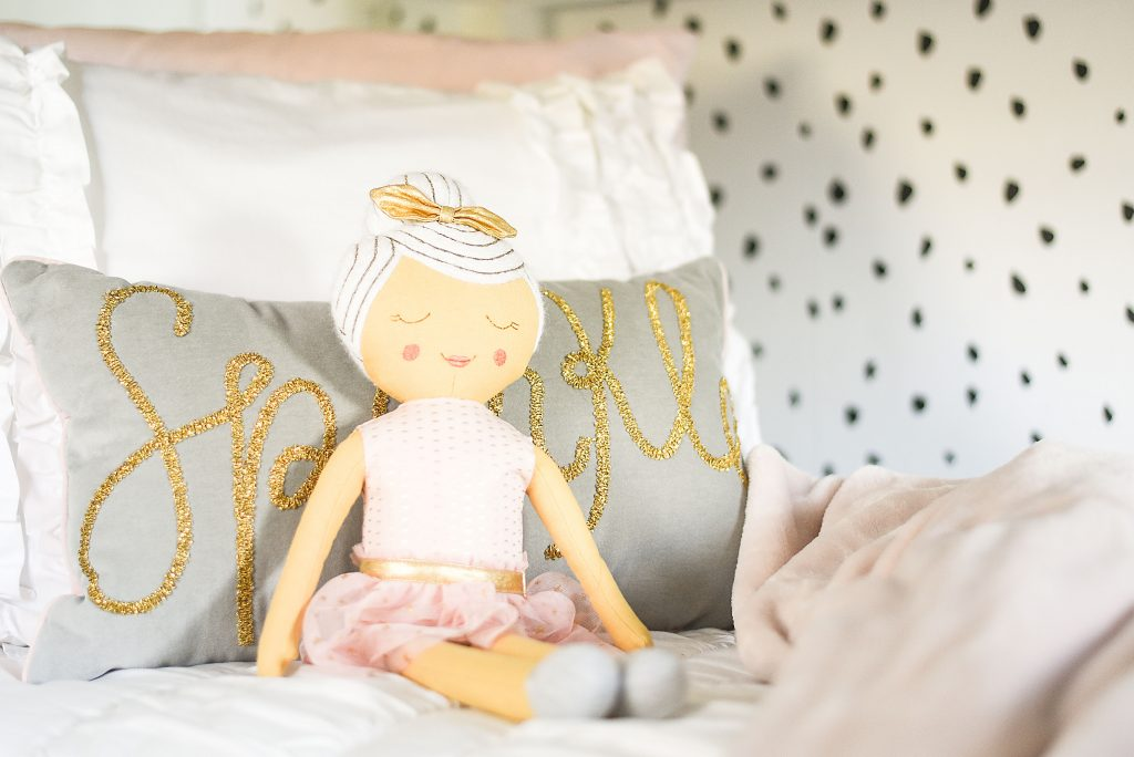 Modern girls bedroom with white, pink and gold color scheme with black and white accent wall with removable wallpaper and pink ballerina doll