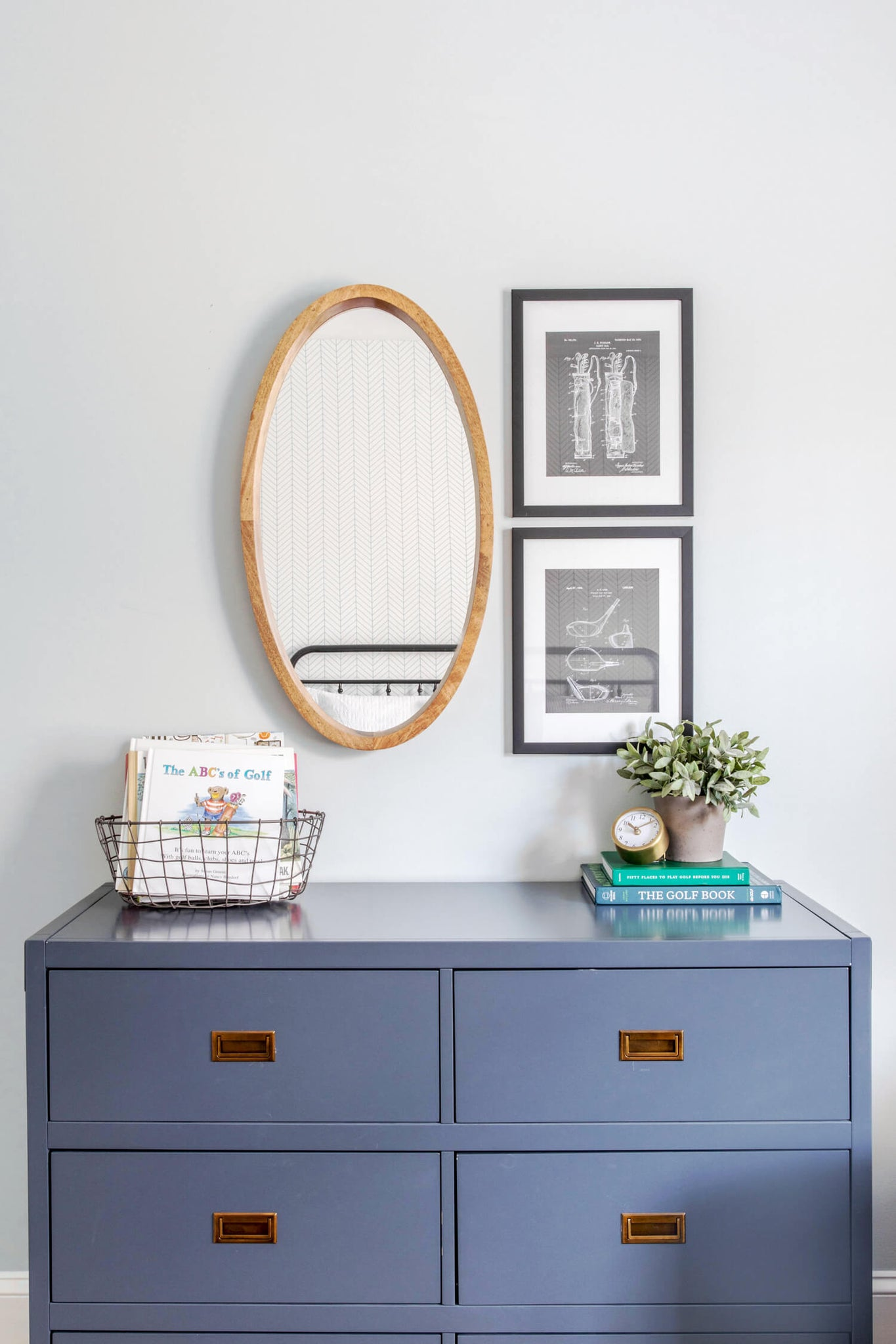Toddler room interior with blue dresser, round wooden mirror and golf theme accents