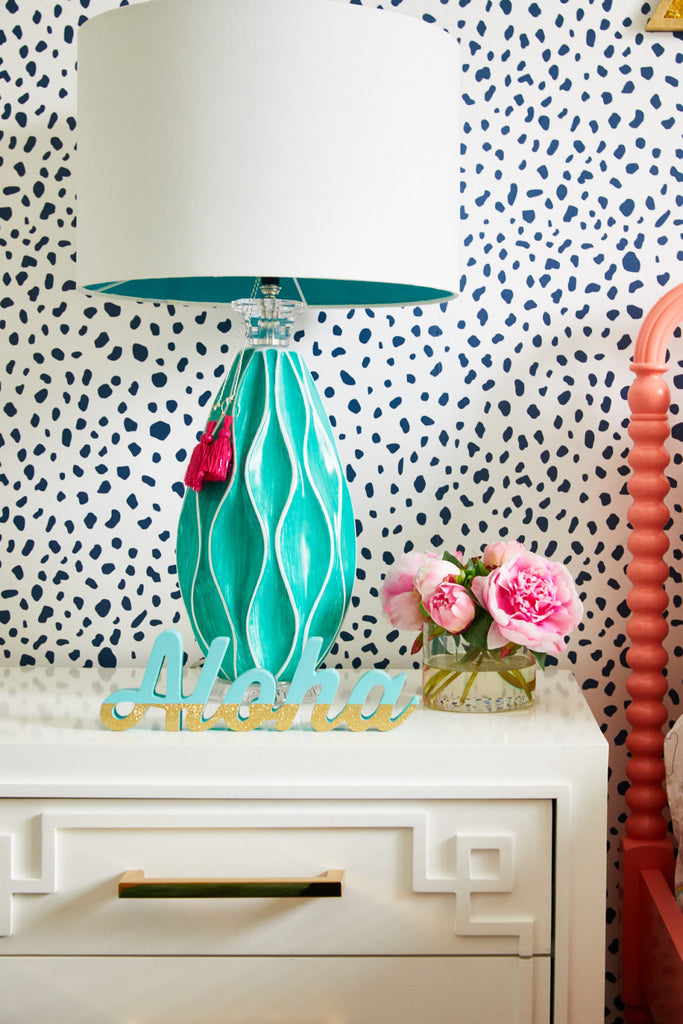 Eclectic bedroom nightstand with turquoise lamp, pink tassels and Aloha sign