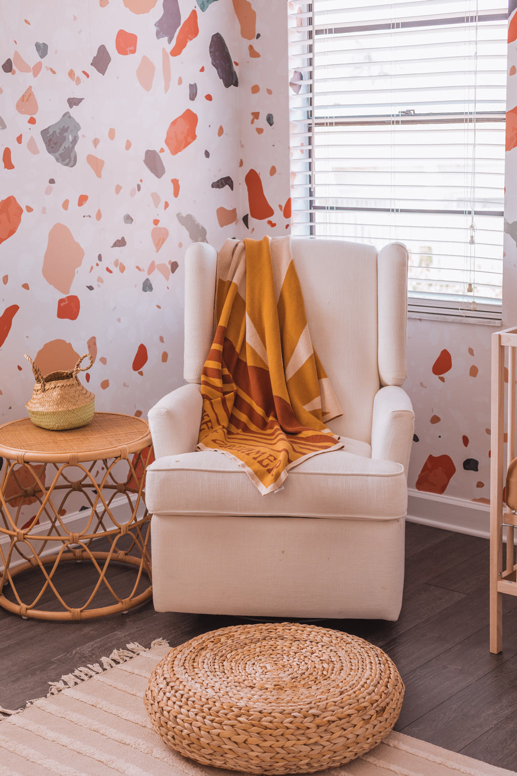 Gender neutral nursery rocking chair corner with terrazzo wallpaper feature wall, warm tone interior decor and woven basket organisation