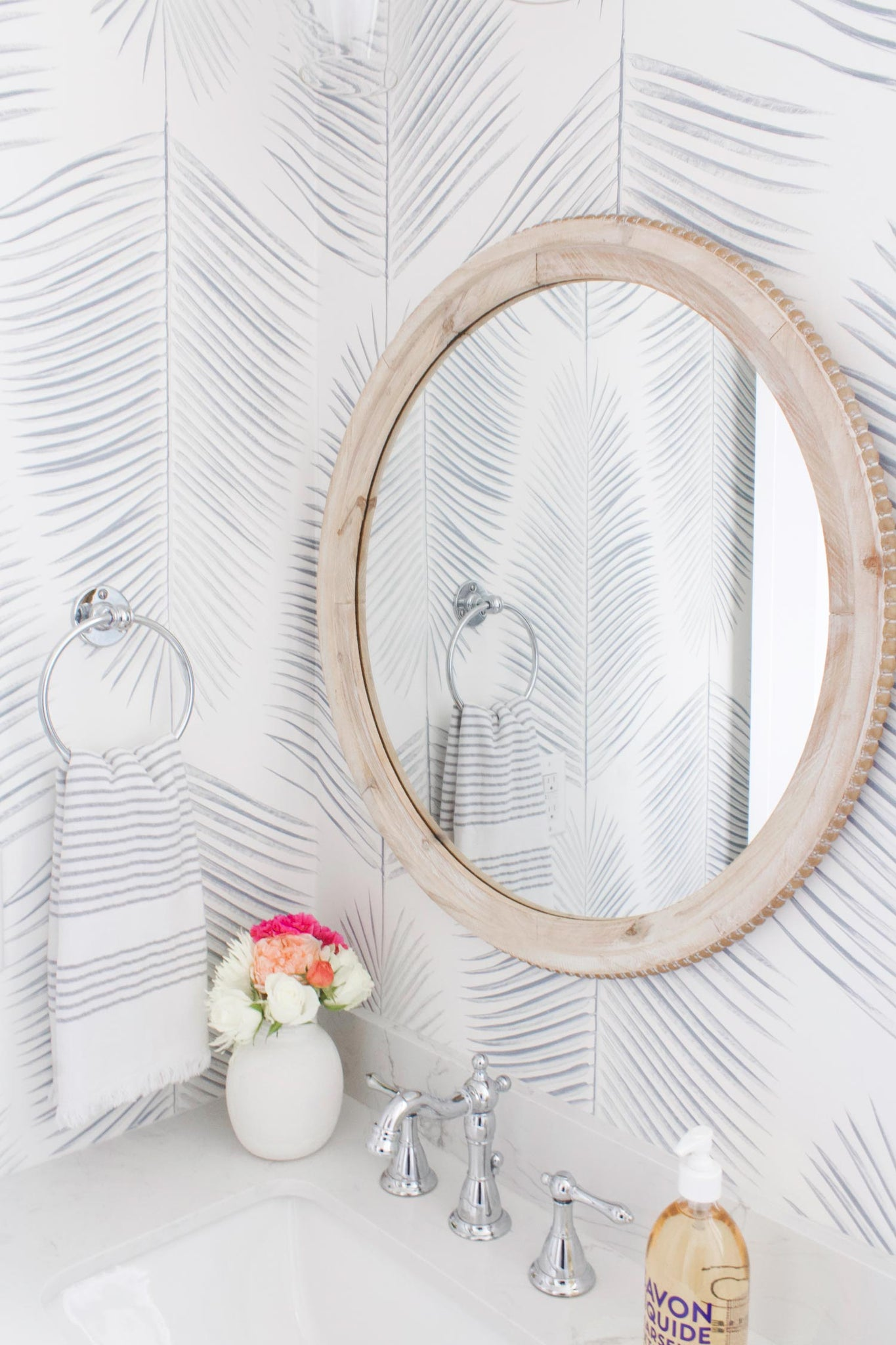 Studio McGee inspired coastal bathroom interior design with marble vanity, farmhouse style faucet and elegant light blue palm leaf design wallpaper