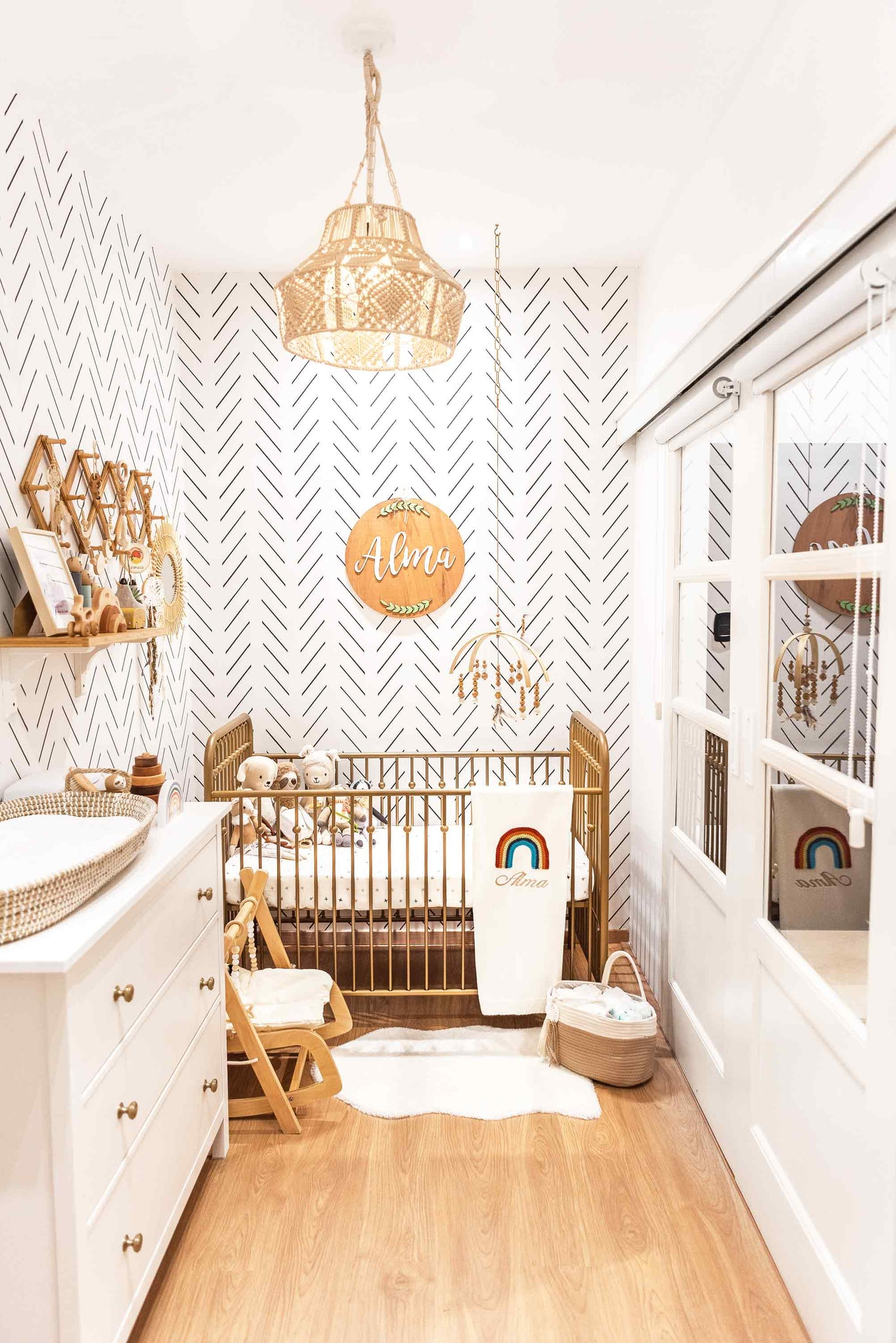 Bohemian style baby girl nursery with white and wood tones, rainbow and animal theme decor and brass color crib