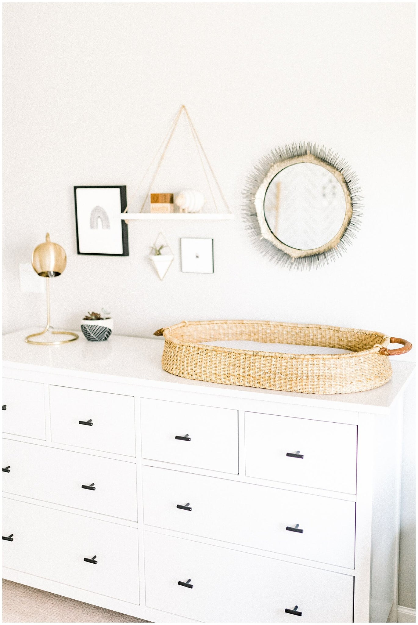 White nursery dresser styled with mid mod interior decor and scandinavian style decor
