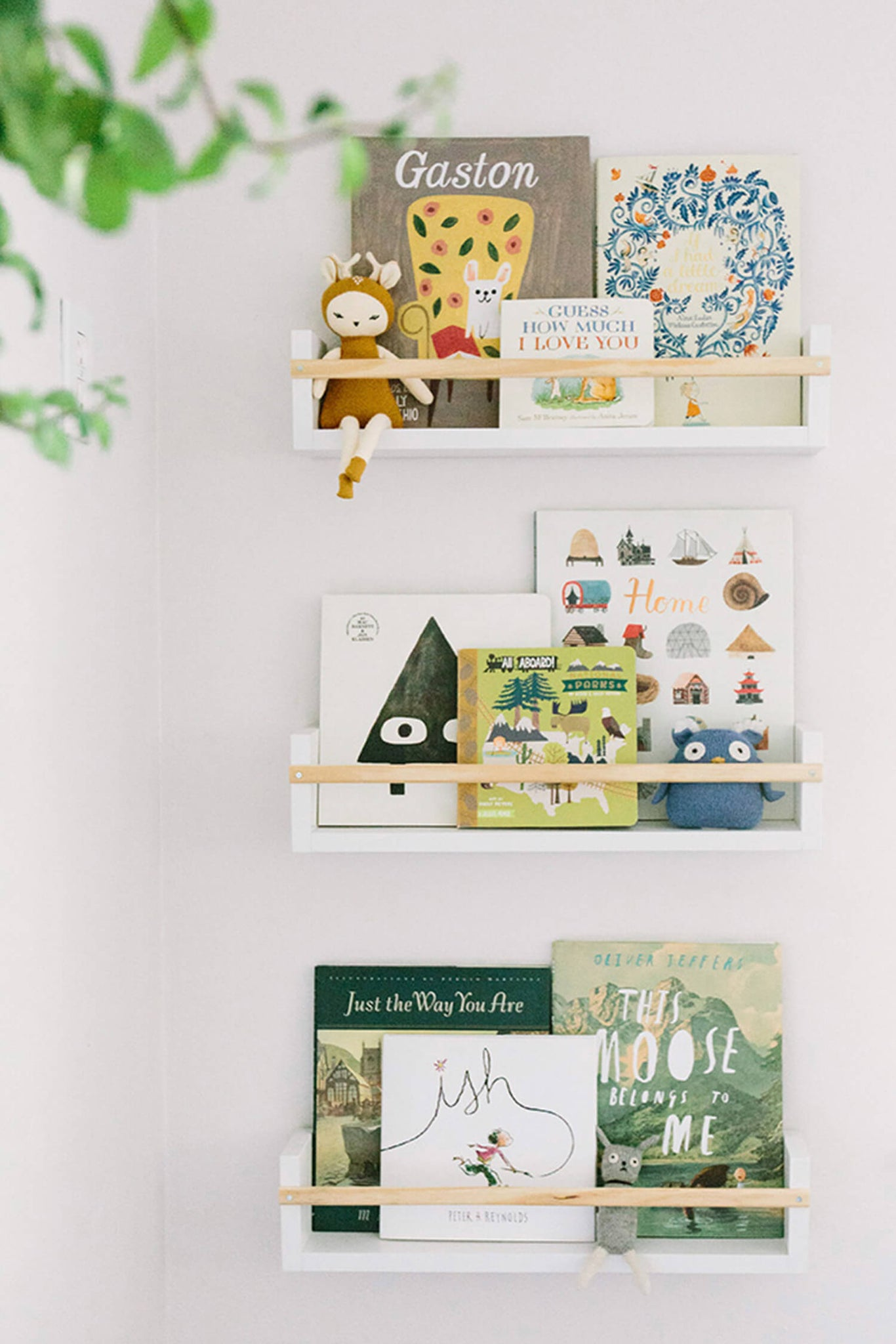 Nursery floating shelves with colorful books, art display.