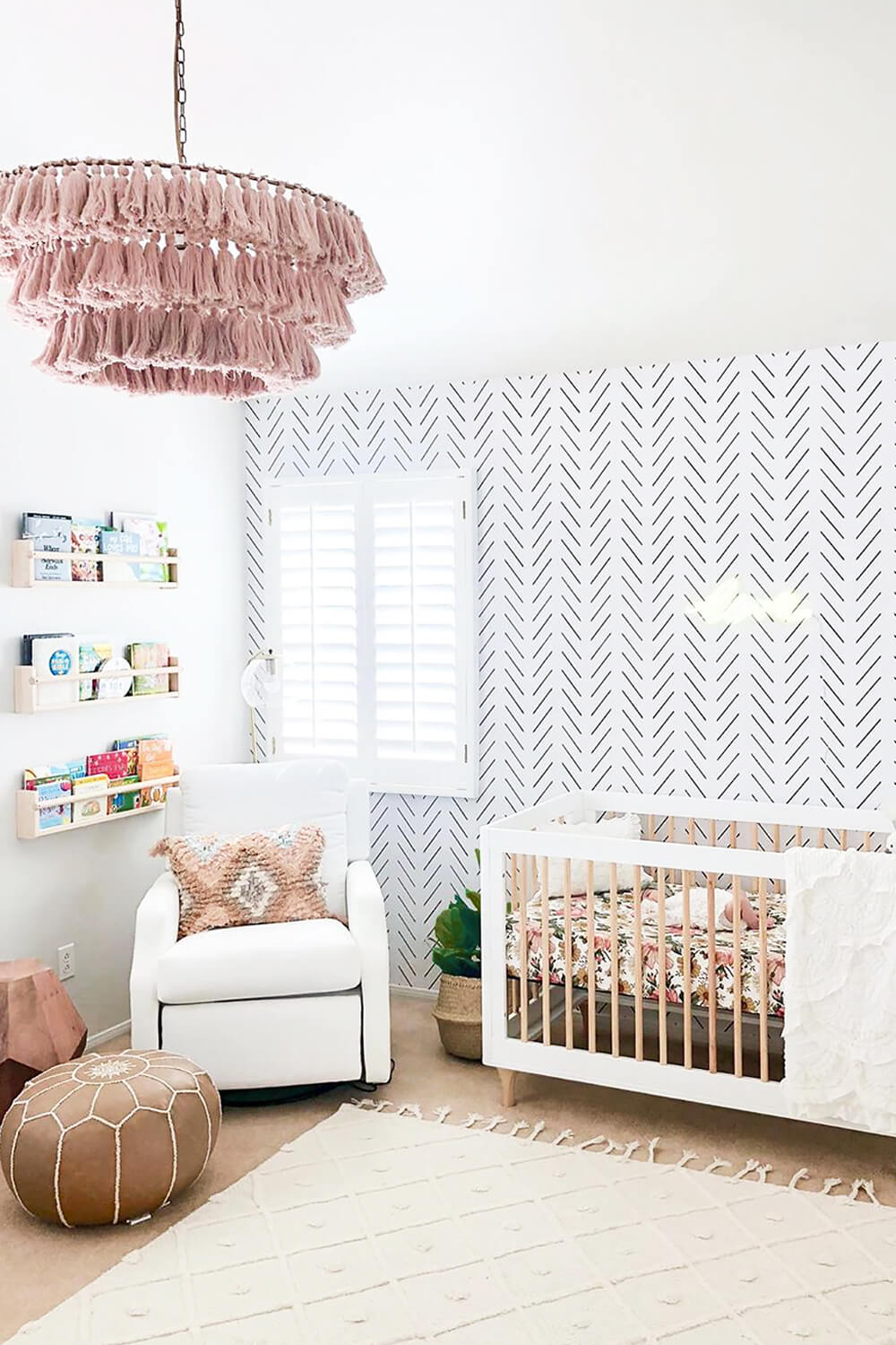 White boho girls nursery interior with delicate herringbone removable wallpaper and blush pink decor