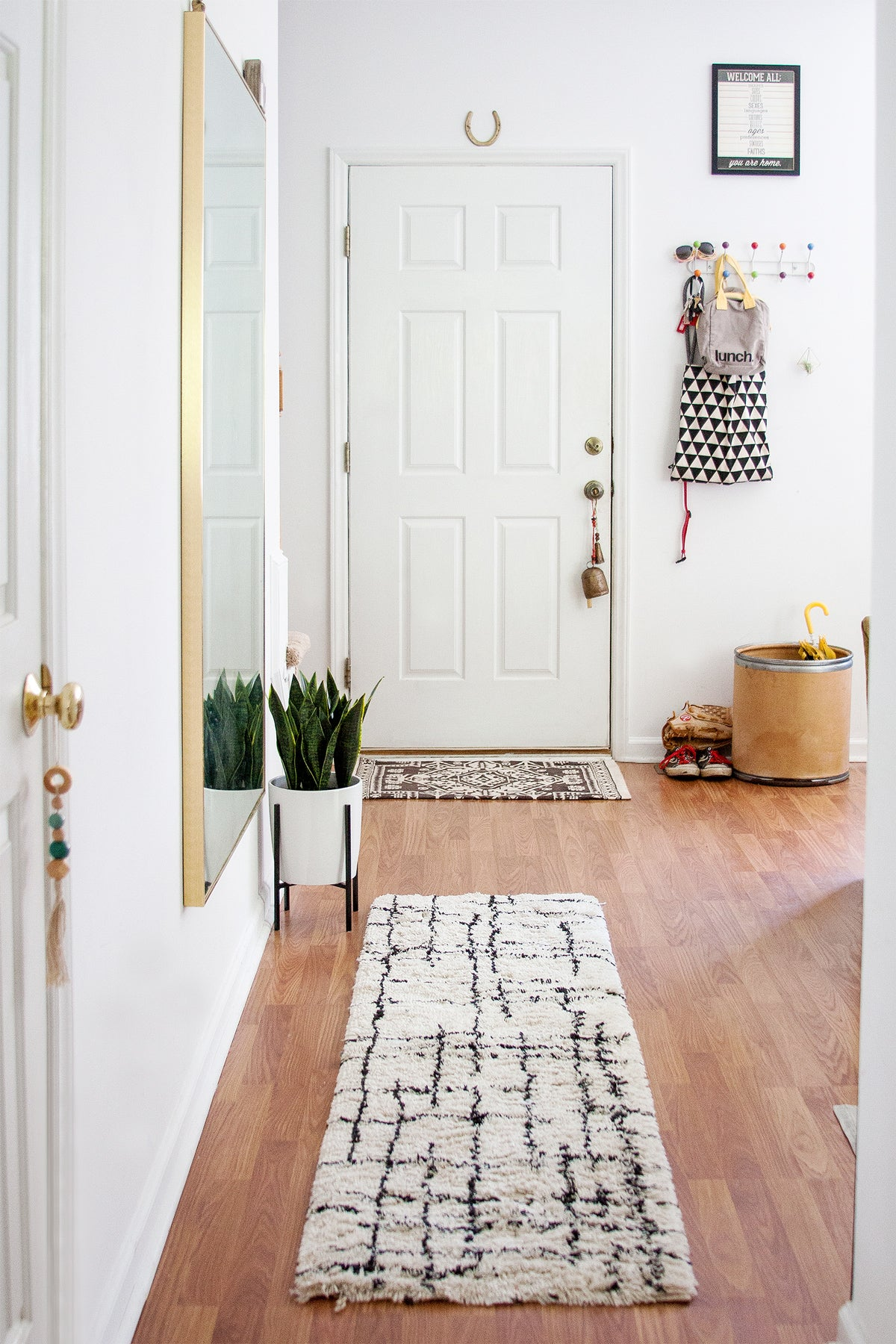 White foyer with moroccan rug and snake plant in an art deco inspired pot