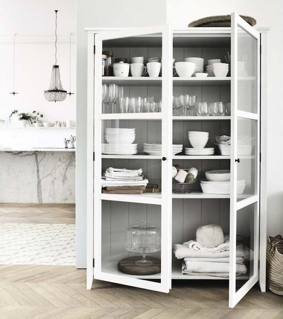 Chic kitchen storage idea, white cabinet with white dinnerware and clear glass decors