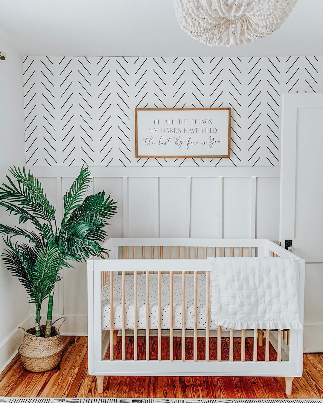 White mid century modern nursery with herringbone removable wallpaper and lush greenery decor