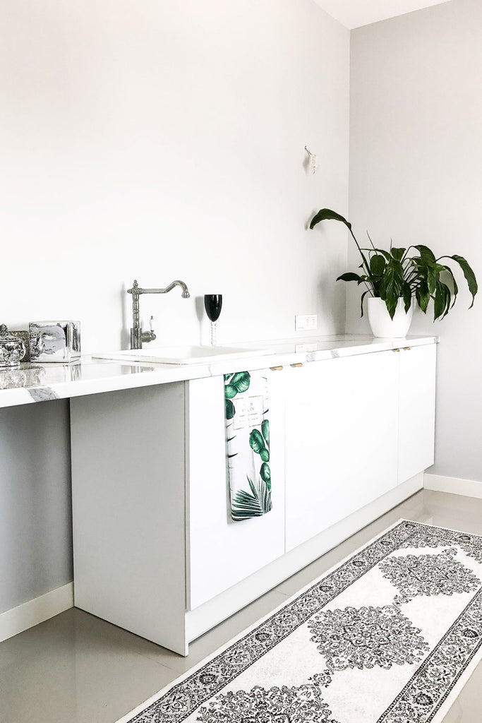 White office kitchen with light grey walls and white oriental rug