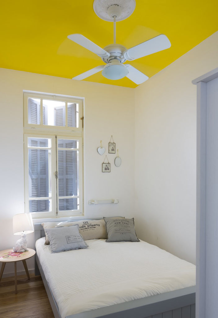 Minimal and light bedroom interior with vibrant yellow ceilings