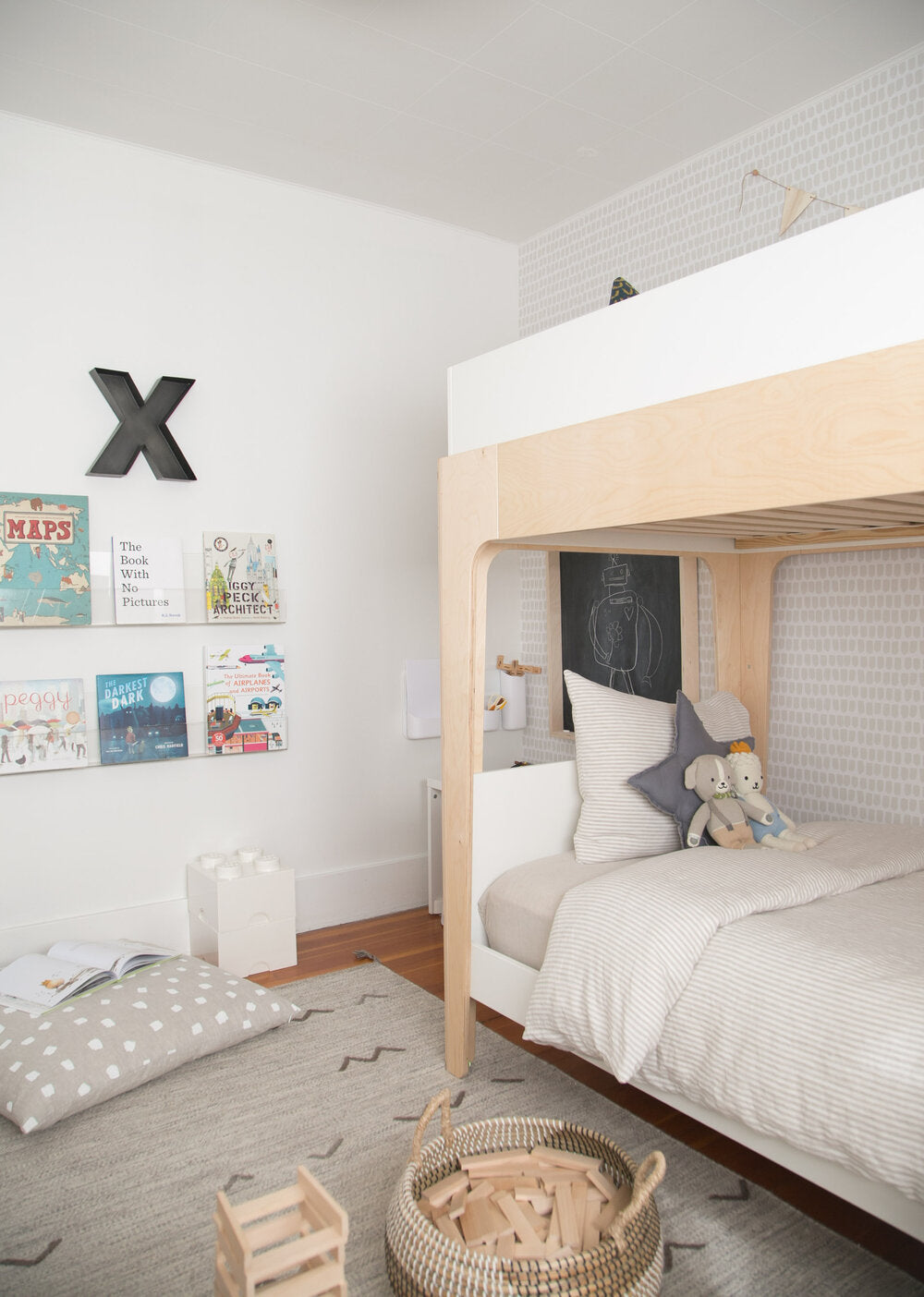 Boys room interior with floating book wall, wood bunk bed, light removable wallpaper and grey color area rug
