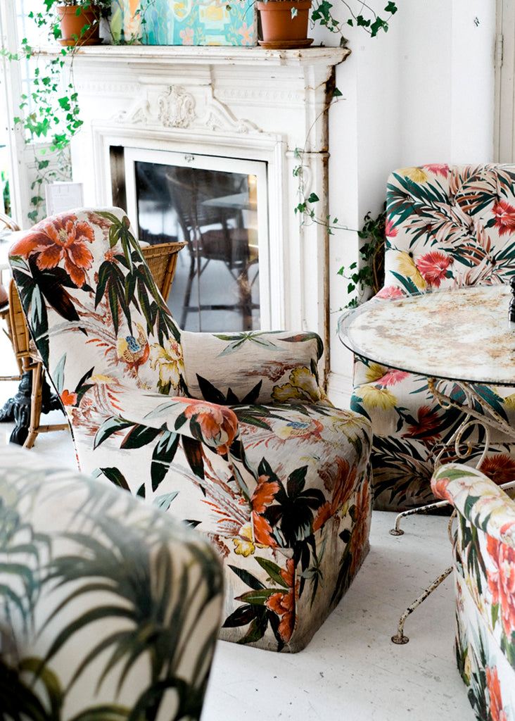 Greenhouse inspired livingroom interior with tropical print chairs and rustic table