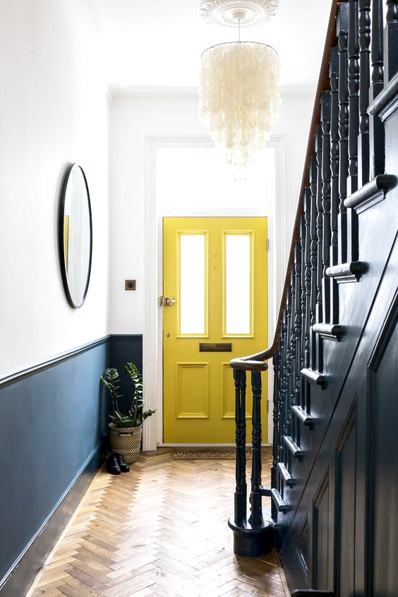 Minimalist entryway with yellow doors and black stairs
