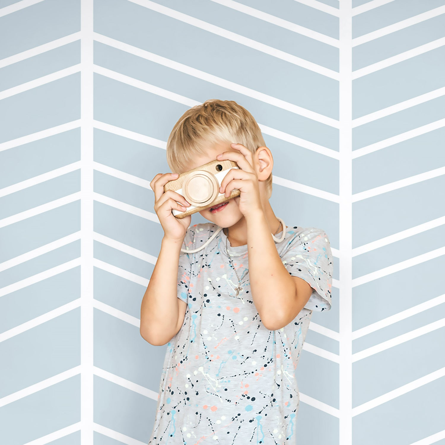 Light blue herringbone wallpaper and boy with toy camera