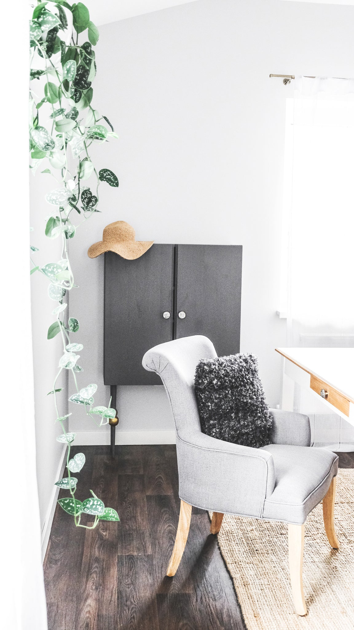 Bohemian workspace with grey armchair and rattan interior decor